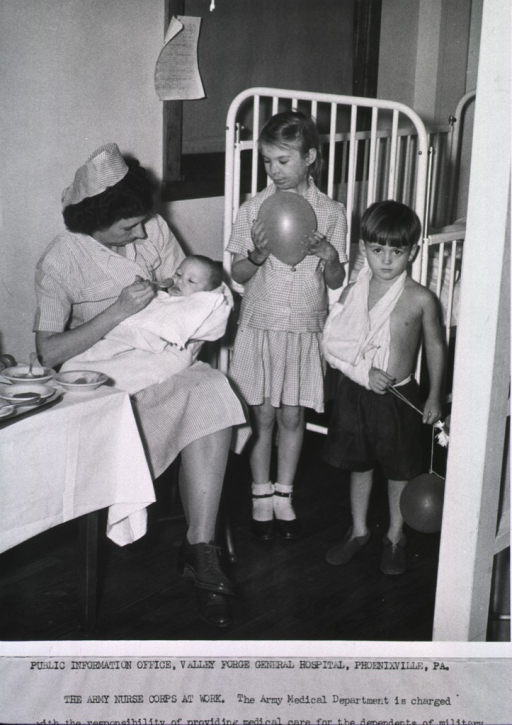 <p>A nurse sits and feeds a baby on her lap, while two other young children, a girl with facial skin grafts and a boy sporting an arm sling, stand by.</p>
