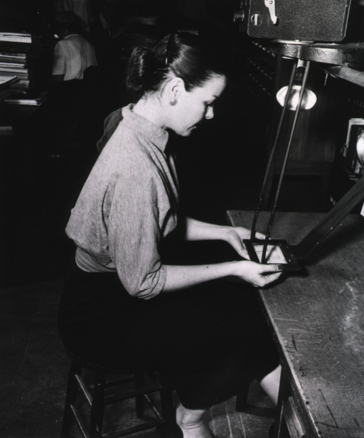 <p>Interior view:  Mrs. Templeton is working with a Kodak Recordak.</p>