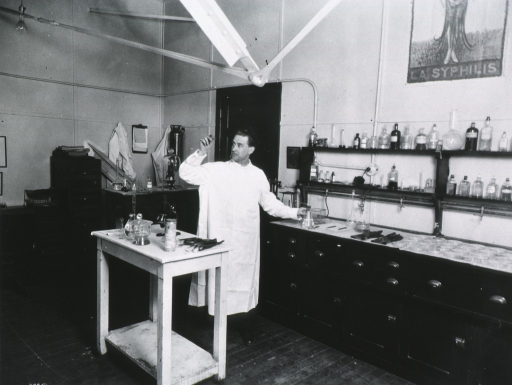 <p>Full length, standing in Syphilis Laboratory, University of Wisconsin, looking at slide.</p>