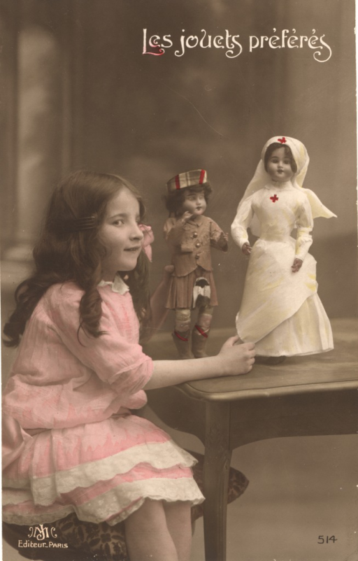 <p>Postcard featuring a hand colored photograph of a girl in a pink dress sitting at a table with two dolls. One doll appears to be a soldier wearing a kilt, and the other is a nurse dressed in white with a red cross on her apron and head covering.</p>