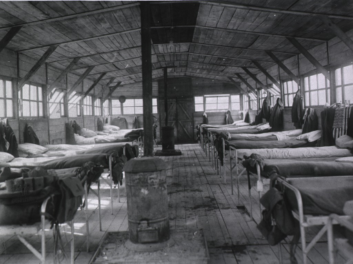 <p>Interior view of wooden structure; looking down a center aisle on each side of which is a row of beds; there are two stoves, for heat, in the aisle.</p>