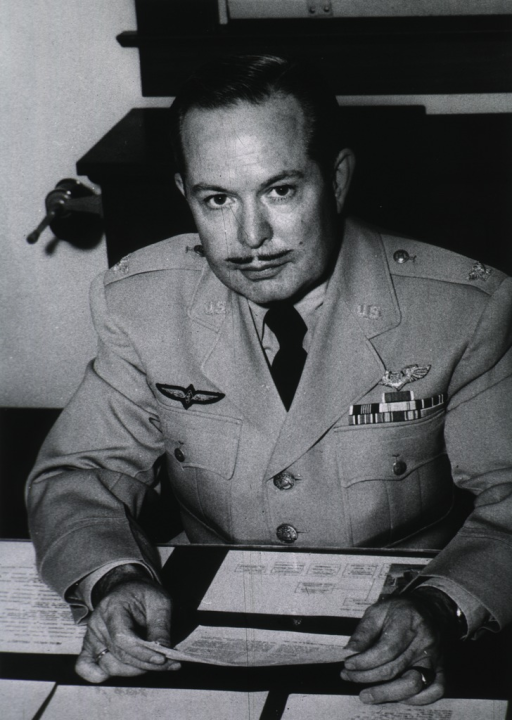 <p>Seated, full face, holding paper, wearing uniform (Colonel).</p>