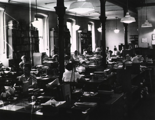 <p>Interior view of Army Medical Library acquisition staff working at their desks; book shelves are against the wall between windows.</p>