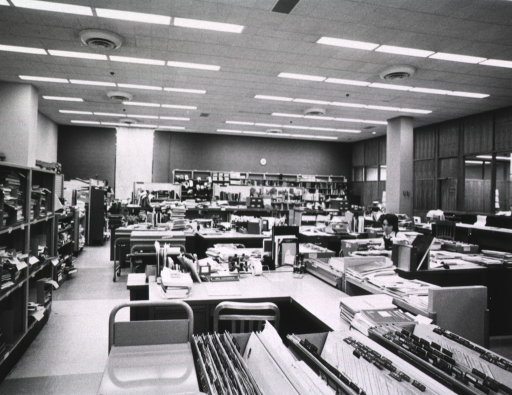 <p>Interior view: Material is stacked on book shelves, book trucks, and on some desks.  In the foreground are journals indexed and index medicus bins with tabs.</p>
