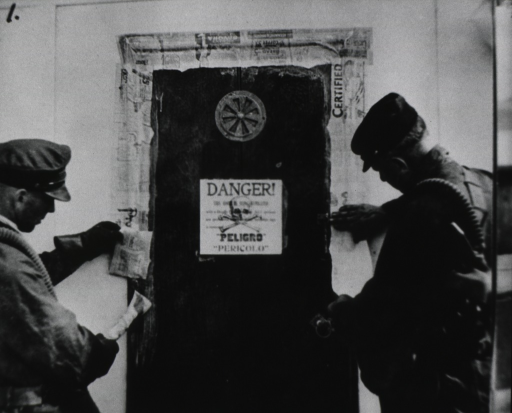 <p>Two men paste paper around a door to seal a compartment on a ship that has just been fumigated. A 'Danger' sign with skull and crossbones is on the door.</p>