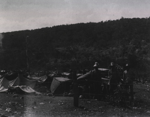 <p>View of a prisoner of war tent camp enclosed with a barbed wire fence; three prisoners(?) are in the foreground.</p>