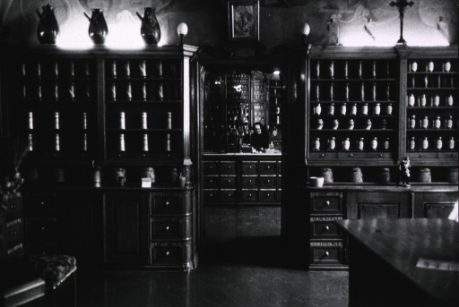 <p>Interior view of the pharmacy; an outer room contains cabinets of apothecary jars; through a doorway into the inner room is seen a nun working behind a counter that has many drawers.</p>