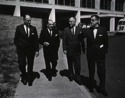 <p>Showing Dr. James A. Shannon, Anthony Celebrezze, Surgeon General Luther Terry, and an unidentified person walking away from Building 31.</p>