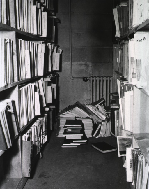 <p>Interior view: Printed material is on shelves and on the floor; a radiator is by the wall.</p>