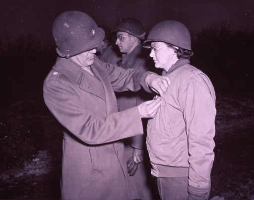 <p>Captain Christine N. Gebhardt, Army Nurse Corps, receives the Bronze Star from Brigadier General John A. Rogers at the 96th Evacuation Hospital, Belgium. (cf. rec. order no. A015147).</p>