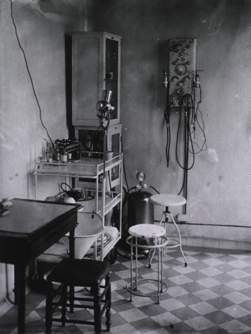 <p>Interior view of clinic showing various pieces of equipment and apparatus against a wall.</p>