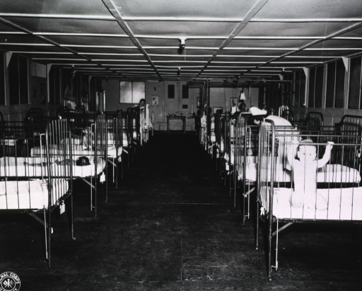 <p>View of a pediatric ward showing two rows of cribs, each containing a child.  Some of the children sleep, others sit, and the child noted in the picture caption grabs the rails of  the crib in an effort to stand.</p>