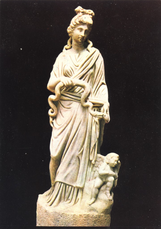 <p>Photograph of an ancient statue of Hygieia holding a snake in her right hand and offering it an egg with her left hand.  The figure of Eros-Hypnos is by her feet.</p>