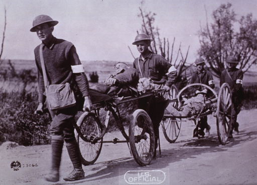 <p>Wheeled stretchers guided and pushed by army personnel.</p>