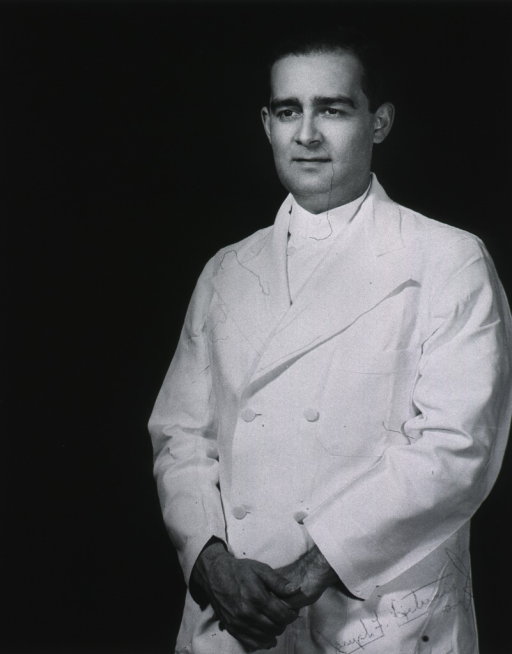 <p>Three-quarter length, full face, standing wearing white coat, hands crossed.</p>