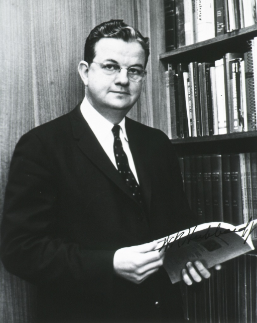 <p>Three quarter length, standing, body to right, face front, holding journal; book shelves in background.</p>