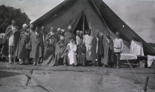 <p>A nurse, patients and staff in front of a tent at Military Mobile Hospital No. 75.</p>