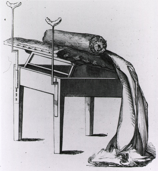 <p>Adjustable table used for gynecological examinations; there are stirrups at the elevated end of the table.</p>