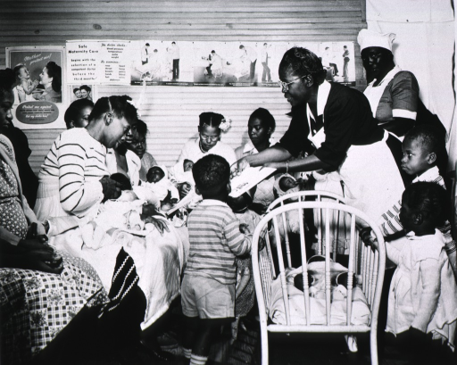 <p>Maude Collen, an African American nurse midwife, offers instruction to new mothers in a nursey.</p>