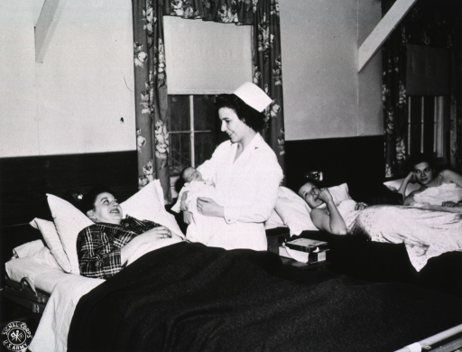 <p>Three women lie on beds in a maternity ward.  The two other women watch as the nurse shows the baby to his mother.</p>