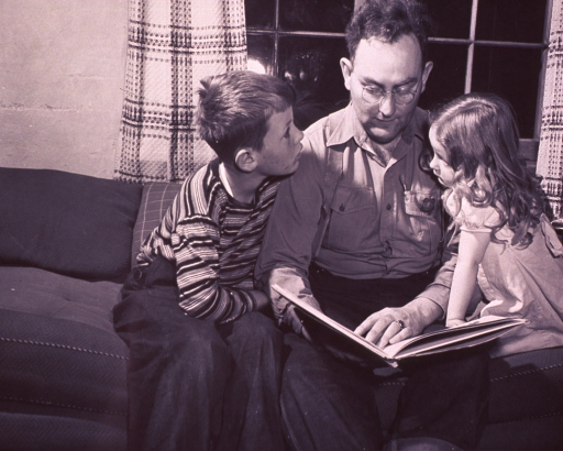 <p>Group portrait of a man (center) in the uniform of a U.S. forest ranger, seated on a sofa reading to his son (left) and daughter (right) from a book he holds in his lap.</p>