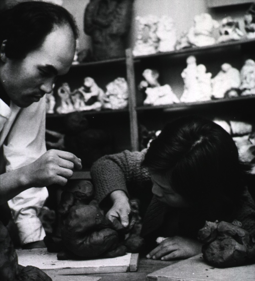 <p>A sculptor is working with a young blind student.</p>