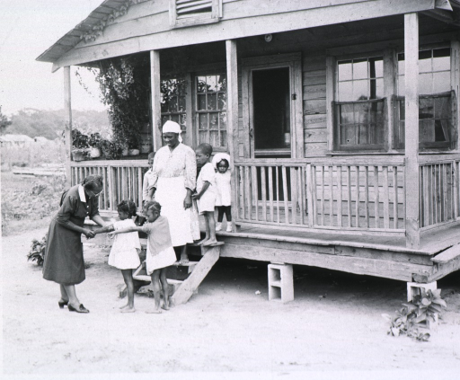 <p>Maude Collen, an African American nurse midwife, visits a home to inspect the children's immunization scars.</p>