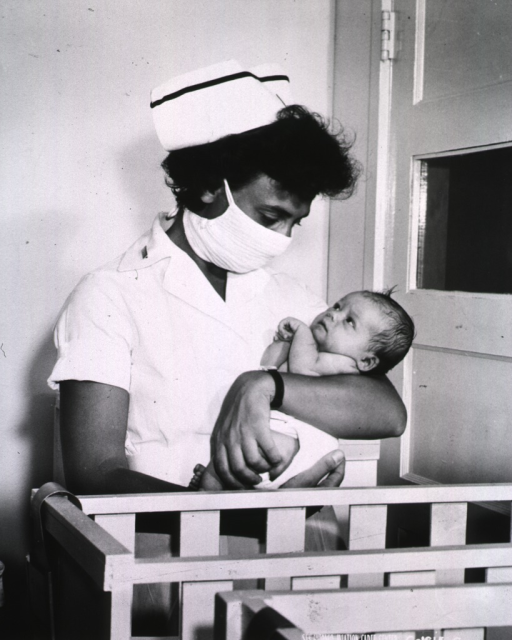 <p>A nurse wearing a mask cradles a baby before placing the baby in a nearby crib.</p>