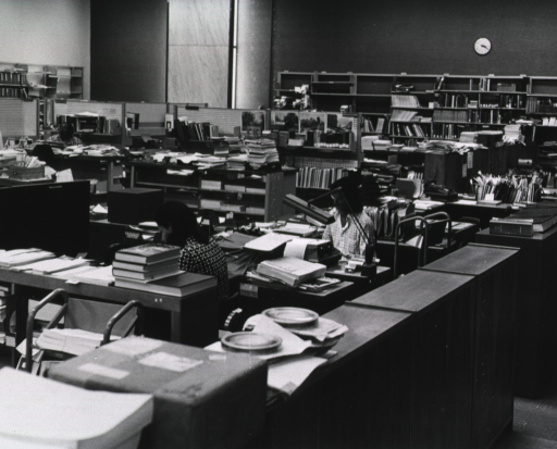 <p>Interior view: a close work space with desks, shelves, narrow book trucks, typewriters, an adding machine, and partitioned areas.</p>