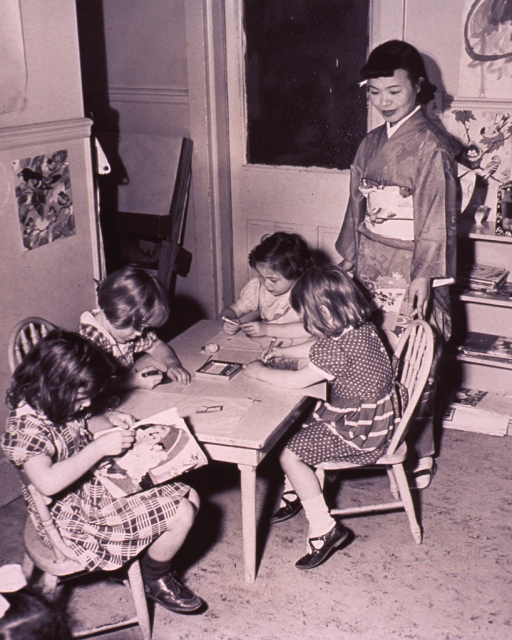 <p>Four children are drawing with crayons.</p>
