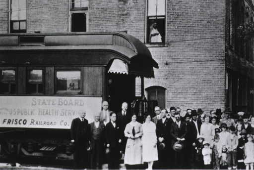 <p>A crowd of men, women, and children are standing near a trolley; in the background is a brick building.</p>