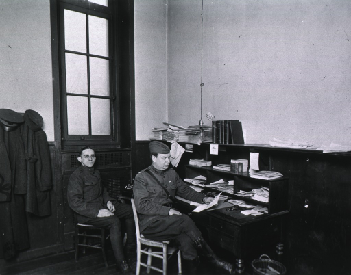 <p>Interior view of Office of Chief of Medical Service, showing Le Boutillier and Pvt. J.R. Botselman seated, right pose, wearing uniforms.</p>
