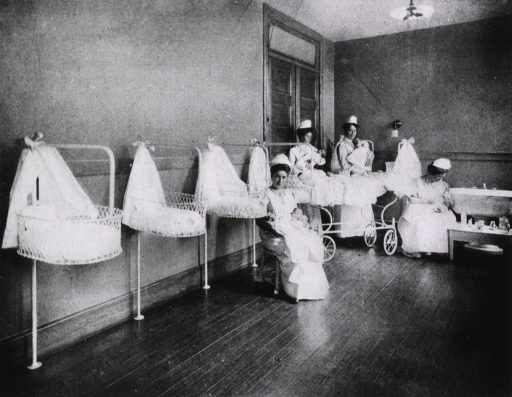 <p>Four nurses hold infants in a large room with baby baskets mounted along one wall.</p>