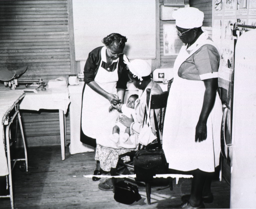 <p>Maude Collen, an African American nurse midwife, is immunizing an infant being held by his mother.</p>
