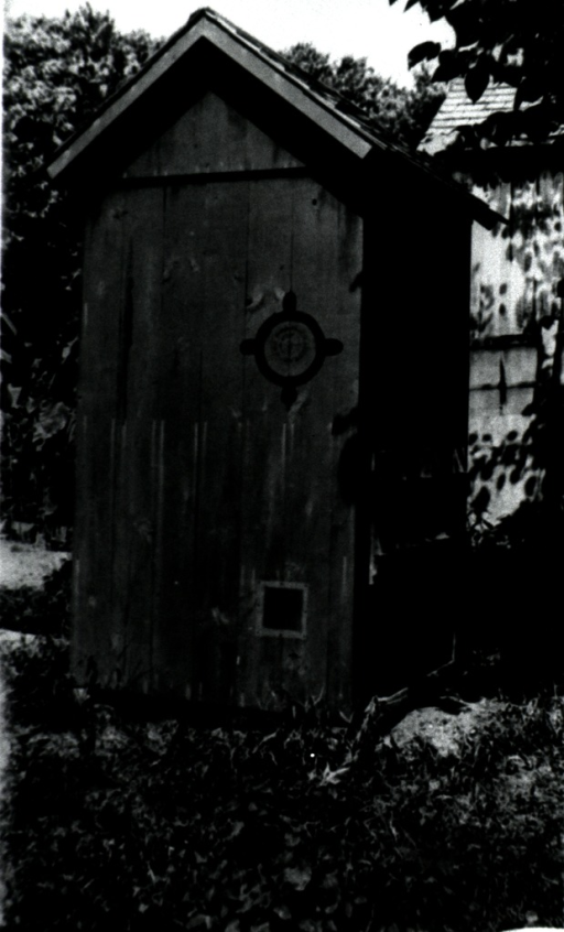 <p>Exterior view of an outhouse; there is an opening on the back wall for removal of the metal container; a logo and a PHS seal are stamped on a side wall.</p>