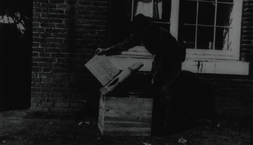 <p>A man wearing PHS field uniform lifts the seat to a type &quot;A&quot; privy box and places a metal container underneath the lid.</p>