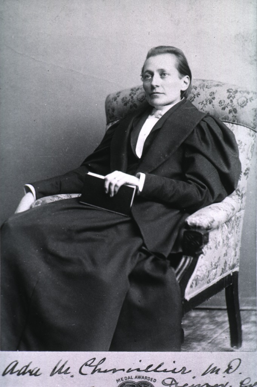 <p>Seated in chair, full face, holding book.</p>
