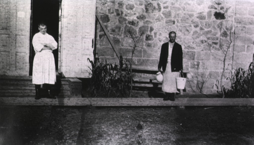 <p>Two &quot;Sanitaries&quot; (hospital attendants) stand outside of a building (hospital?).  One is carrying a bucket and pitcher.</p>