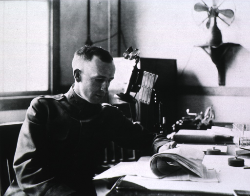 <p>Half-length, seated at desk, right pose; holding and reading papers on the desk.</p>