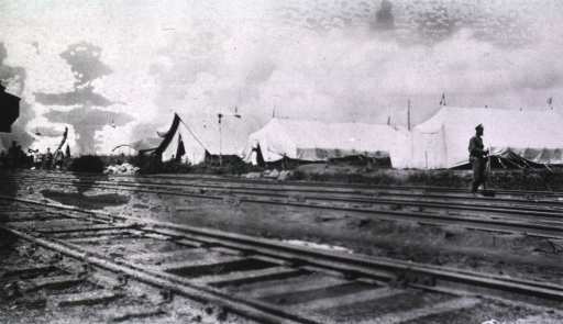 <p>A view of the Vitebsk Red Cross Hospital.  A soldier(?) walks on the railroad tracks.</p>