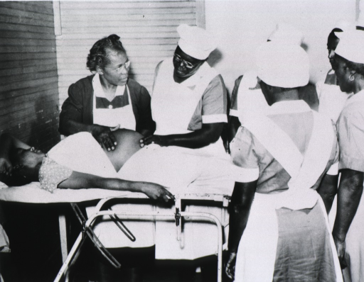 <p>Maude Collen, an African American nurse midwife, is conducting a class at the State Board of Health's Midwife Institute at Frogmore around 1950.  A pregnant woman is on a stretcher and a group of students are standing around the stretcher.</p>