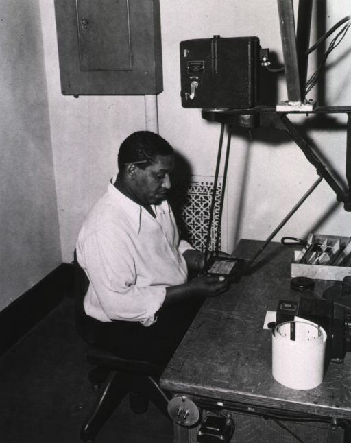 <p>Interior view:  Acquisition Division.  Mr. Jordan using an Eastman Kodak Recordak camera.</p>
