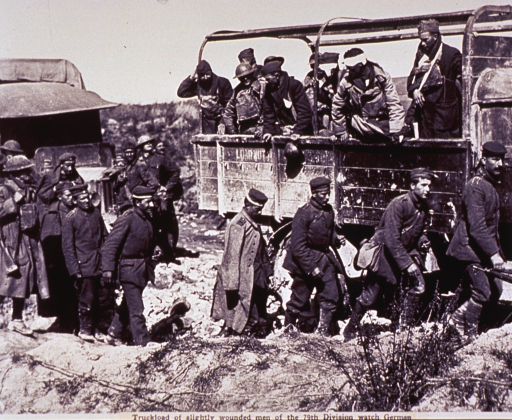 <p>Group of soldiers standing in a truck watch as a line of German prisoners passes by on the side of the roadway.</p>