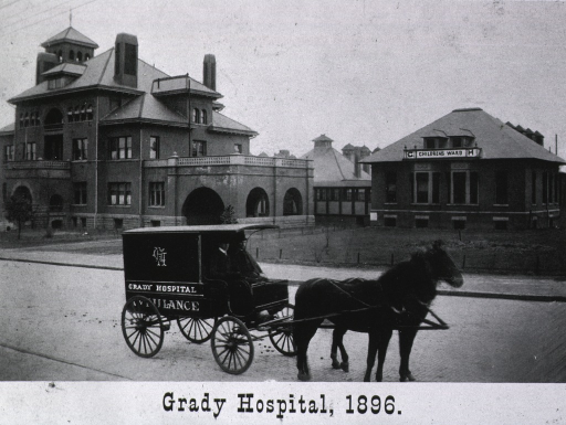 <p>Exterior view showing cluster of buildings (childrens ward is to the right), and a horse-drawn ambulance is in the foreground.</p>