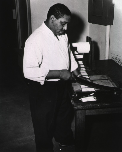 <p>Interior view: Mr. Jordan is using a paper cutter in the Acquisition DIvision.</p>