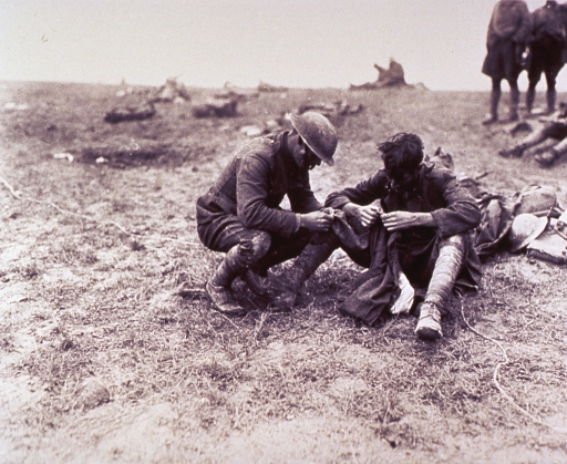 <p>Close-up of two soldiers in uniform sitting on the ground examining an article of clothing for the presence of lice.</p>