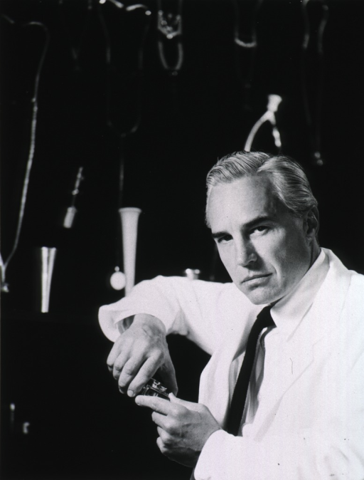 <p>Half-length, full face, wearing lab coat, showing stethoscopes hanging on a wall behind him.</p>