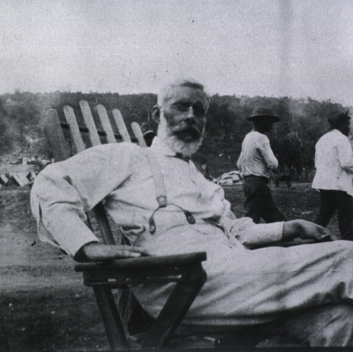 <p>Three-quarter length, seated, right pose, full face; out-of-doors; tents in background.</p>