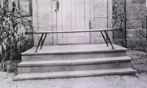 <p>A hospital bed on the steps of the entrance to the hospital(?).</p>
