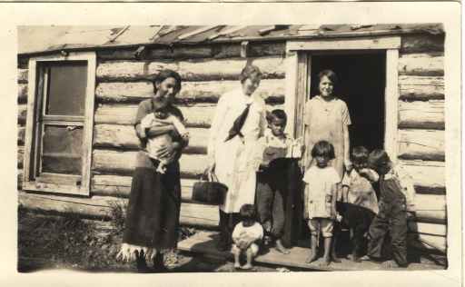 <p>Miss Eggestine(?), White Earth Indian Reservation Nurse, making a home health call.  In addition to the nurse, two Indian women and several children are shown standing at the doorway to the home.</p>